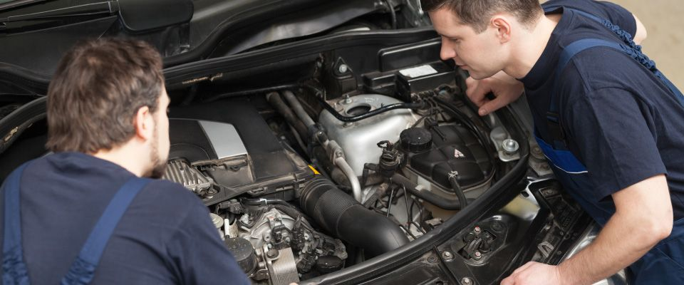 2 mechanics servicing car